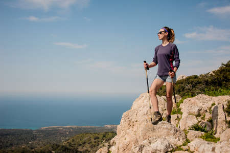 Photo for Attractive girl standing on the rock in shorts with walking sticks - Royalty Free Image