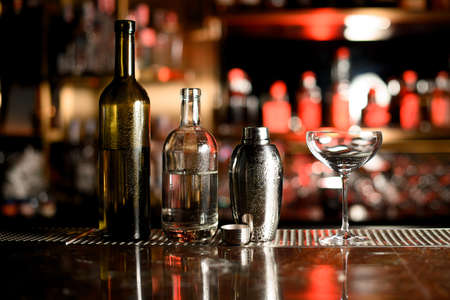 Photo for Two bottles, shaker and glass on bar counter - Royalty Free Image