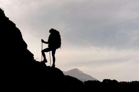 Photo pour Silhouette of female hiker climbing on mountain - image libre de droit