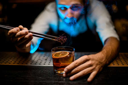 Photo pour Professional bartender adding chilled brown caramel with twezzers to the cocktail with ice cubes under blue light - image libre de droit