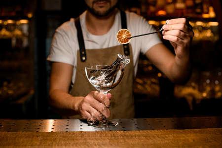 Photo for Close-up of bartender decorating splashing alcohol with orange - Royalty Free Image