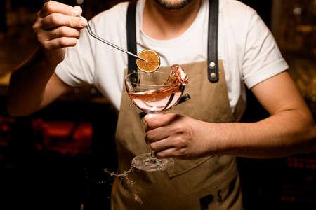 Foto de Professional male bartender adding to an alcoholic cocktail a dried lemon with tweezers - Imagen libre de derechos