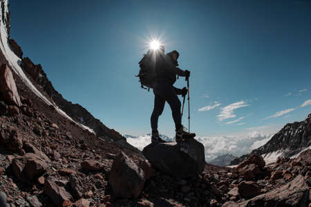 Photo pour Man standing on the rock around the snow remnants under the sun in clear sky - image libre de droit