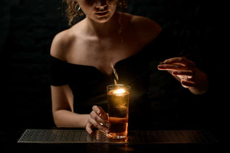 Photo for attractive sexy girl at bar decorates glass with alcoholic drink by spikelet. - Royalty Free Image