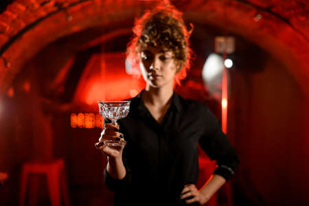Foto de Young woman holds empty glass in front of her and looks at it. - Imagen libre de derechos