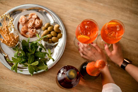 Foto de Top view on the table with glasses of cold bright orange drink which female hands hold - Imagen libre de derechos