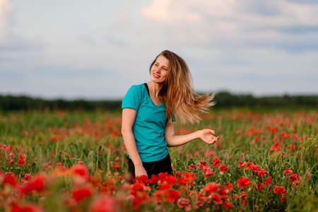 Photo for young smiling woman with long hair standing on field with red poppies. - Royalty Free Image