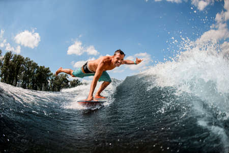 Photo for happy man stands on surfboard leaning on one leg and arm - Royalty Free Image