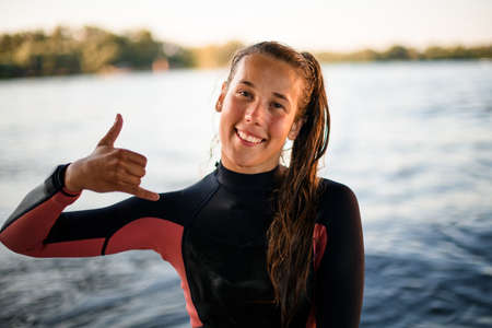 Photo pour cheerful young woman shows hand gesture on the background of the river water - image libre de droit