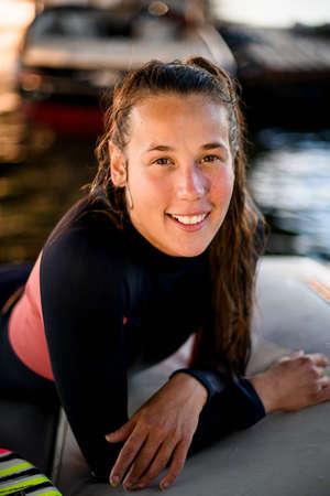Photo pour portrait of smiling athletic young woman with wet hair wearing a black wetsuit - image libre de droit