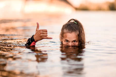 Photo pour head of young woman half emerges from the water and her hand shows gesture - image libre de droit