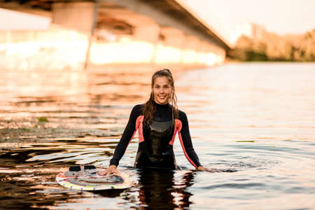 Photo pour young smiling woman in black wetsuit stands in the water. - image libre de droit