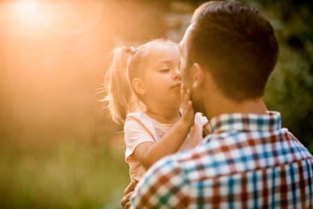Photo pour Rear view of man holding his daughter in his arms on sunny summer day. - image libre de droit
