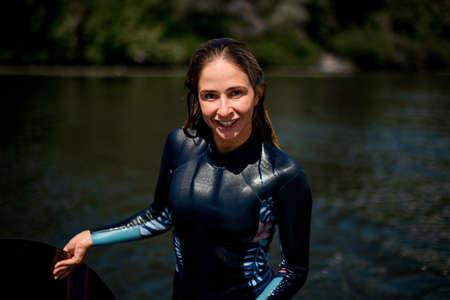 Photo pour smiling woman in wetsuit stands on the background of the river water - image libre de droit