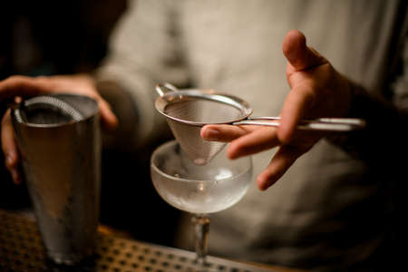 Photo pour close-up on hand of bartender in which he holds sieve over wine glass - image libre de droit