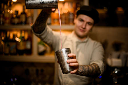 Photo pour young barman holds shaker glasses in his hands and pours cocktail from them - image libre de droit