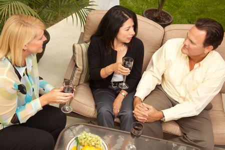 Three Friends Enjoying Wine on an Outdoor Patio.