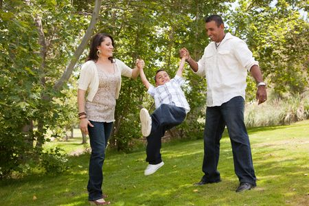 Hispanic Man, Woman and Child having fun in the park.