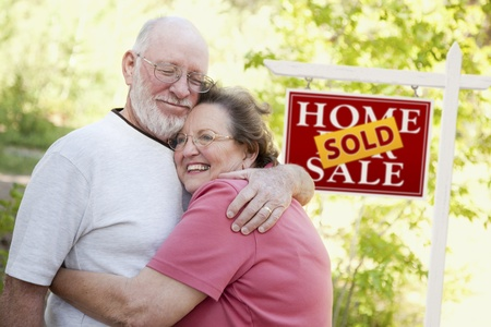 Happy Affectionate Senior Couple Hugging in Front of Sold Real Estate Sign.