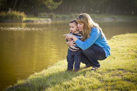 Happy Mother and Baby Son Looking Out At The Pretty Lake.