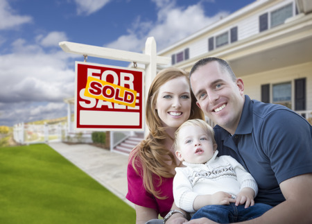 Happy Young Military Family in Front of Sold Real Estate Sign and New House.