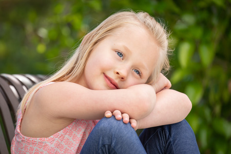 Photo pour Pretty Young Caucasian Girl Portrait Sitting On The Bench At The Park. - image libre de droit