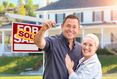 Photo pour Happy Couple With New House Keys In Front of Sold Real Estate Sign and Beautiful House. - image libre de droit