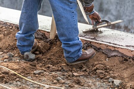 Photo pour Construction Worker Using Wood Trowel On Wet Cement Forming Coping Around New Pool. - image libre de droit