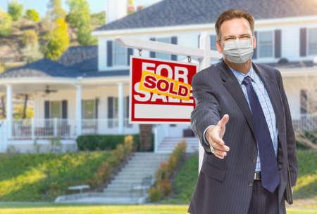 Foto de Male Real Estate Agent Reaching for Hand Shake Wearing Medical Face Mask with Sold For Sale Sign Behind. - Imagen libre de derechos