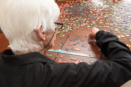 A thousand piece jigsaw puzzle put together by a white haired elderly retired white womanの写真素材