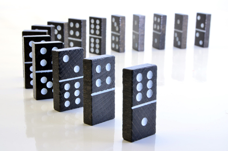 picture of black dominoes standing in a row
