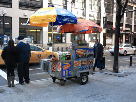 New York - March 6, 2015: A Manhattan hot dog stand with umbrellas.