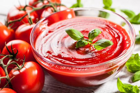 Tomato sauce with basil leaf in a glass bowl and red tomatoes