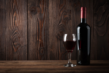 Red wine bottle and glass of wine on the dark wooden background, studio light