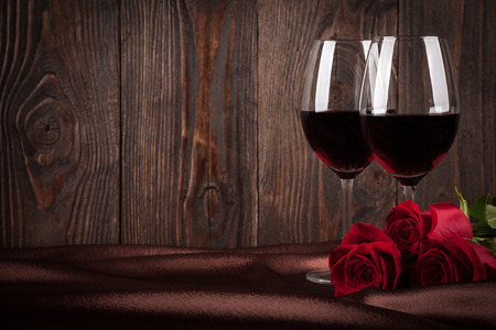 Foto de Two glasses of red wine and red roses on brown silk - Imagen libre de derechos