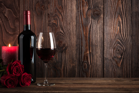 Foto de Red wine bottle, glass of wine, candle and roses on wooden background - Imagen libre de derechos