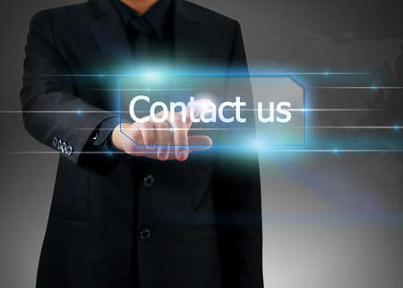 businessman pushing on contact us button.