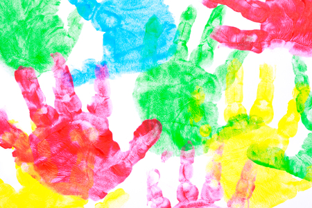 Multicolored painted hand prints on a white background red, yellow, blue and red colors