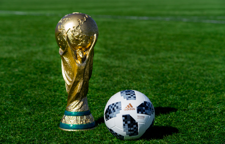 Photo pour April 9, 2018 Moscow, Russia Trophy of the FIFA World Cup and official ball of FIFA World Cup 2018 Adidas Telstar 18 on the green grass of the football field. - image libre de droit