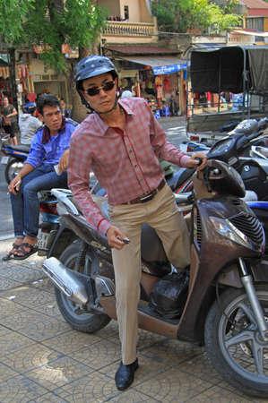 Hanoi, Vietnam - June 1, 2015: man is leaving his scooter on the street in Hanoi