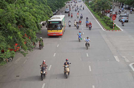 Hanoi, Vietnam - June 2, 2015: scooters and cars on the road in Hanoi
