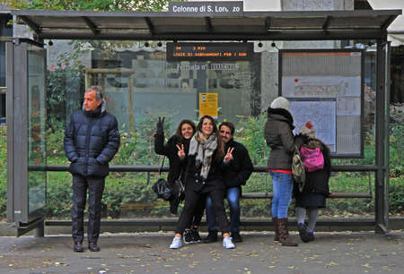 Milan, Italy - November 28, 2015: people are waiting for bus on stop station in Milan