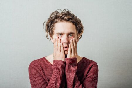 Closeup portrait, headshot young tired, fatigued business man worried, stressed, dragging face down with hands, isolated , grey background. Negative human emotions, facial expressions, feelings