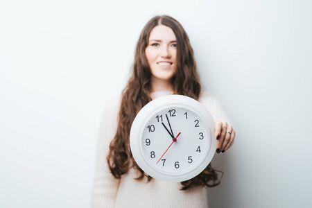 Foto de on a white background girl holding a clock in his hands - Imagen libre de derechos
