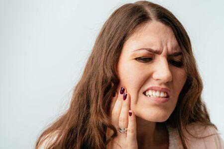 Photo pour long-haired beautiful brunette girls have a toothache - image libre de droit