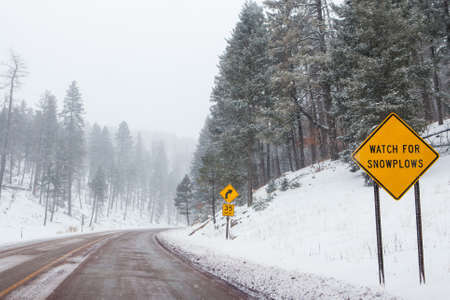 A snowy mountain road with warning signs in Cloudcroft, New Mexico, USA