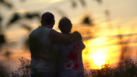 Photo pour Man and woman embracing each other looking at the sunset. The woman put her head on the man's shoulder - image libre de droit