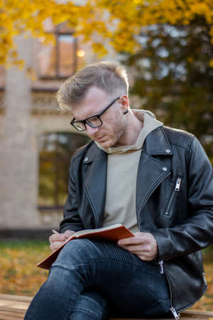 Photo for Guy writer in casual clothes makes notes in a notebook and sits on a park bench near the university, a successful student in black glasses and a jacket does homework - Royalty Free Image