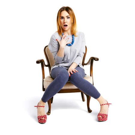 Studio shot of offended woman sitting on armchair.