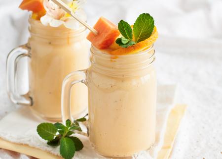 Photo for Homemade smoothie with tropical fruits: mango, banana, pineapple, papaya in glass Mason jar. Healthy juicy vitamin drink - Royalty Free Image